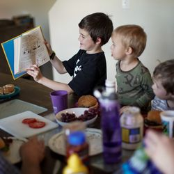 Elijah Newbold, 7, shows a book to his brothers, Isaac, 2, and Asher, 5, while eating dinner at their home in Kaysville on Tuesday, April 7, 2020.