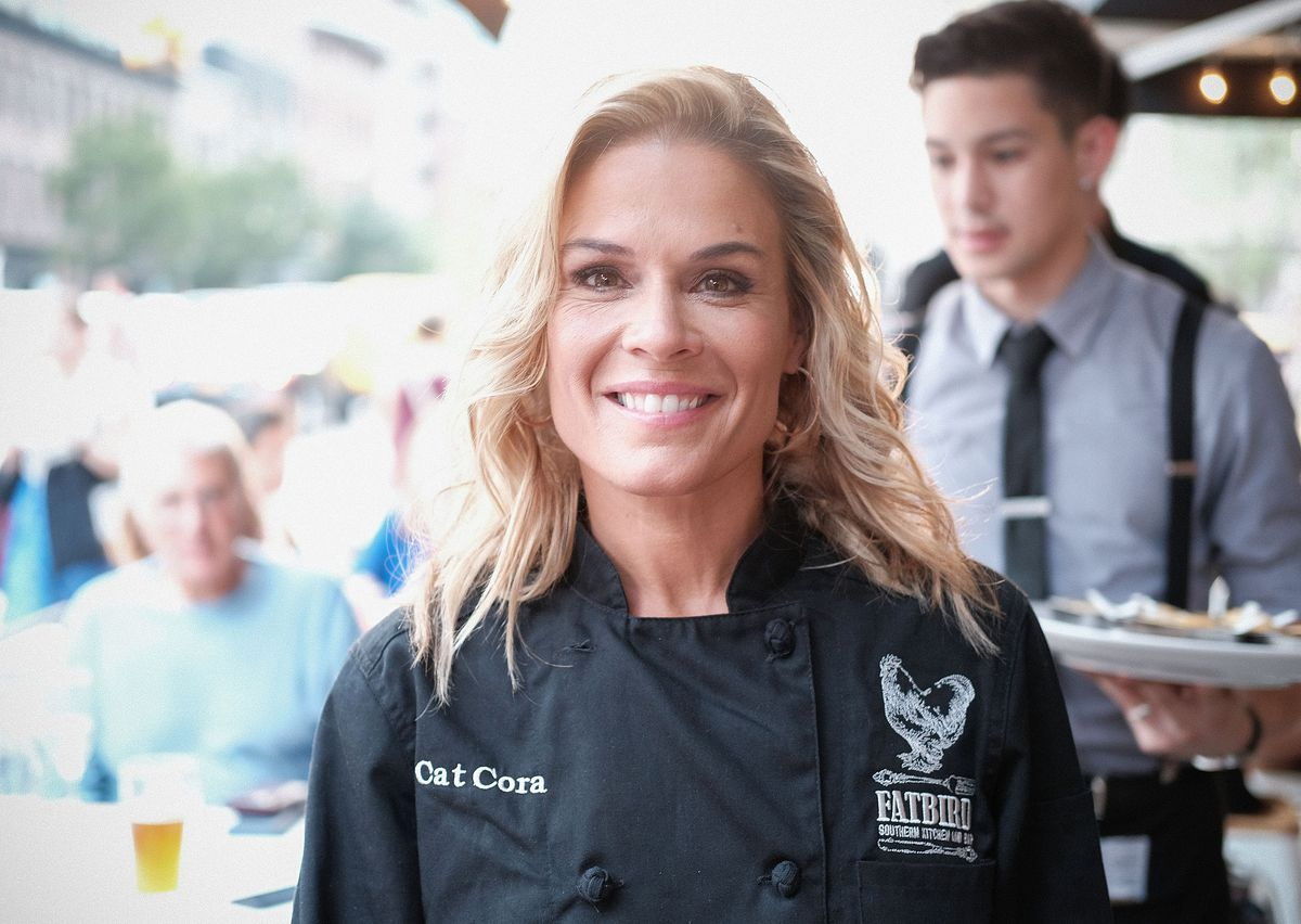 """Chef Cat Cora wearing a black chef coat bearing the words """"Fatbird."""""""