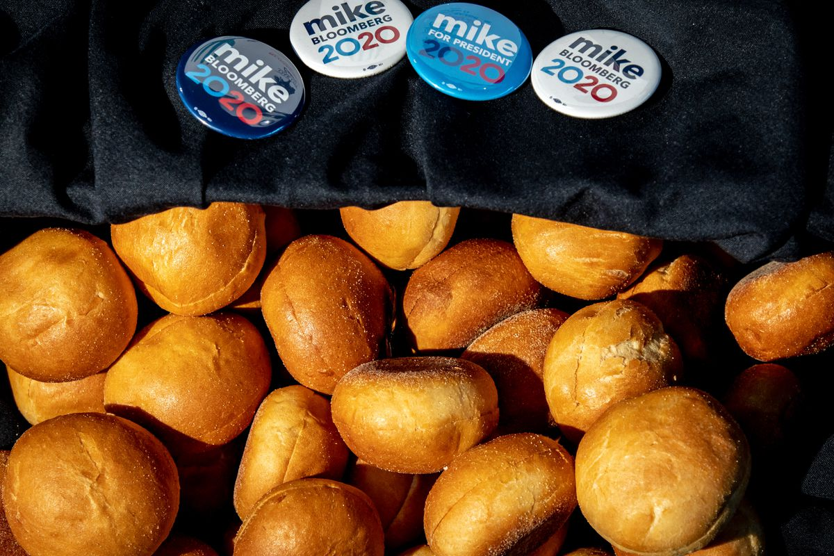 "A pile of bread rolls sits next to campaign buttons reading ""Mike Bloomberg 2020."""