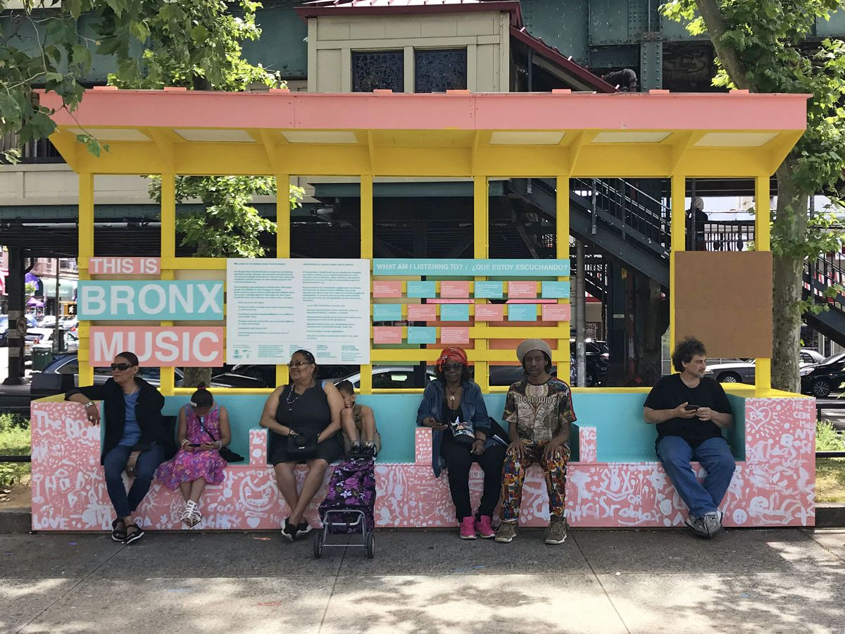 """A colorful seating area—pink, blue, and yellow—with a cover and a sign that says """"Bronx Music."""""""
