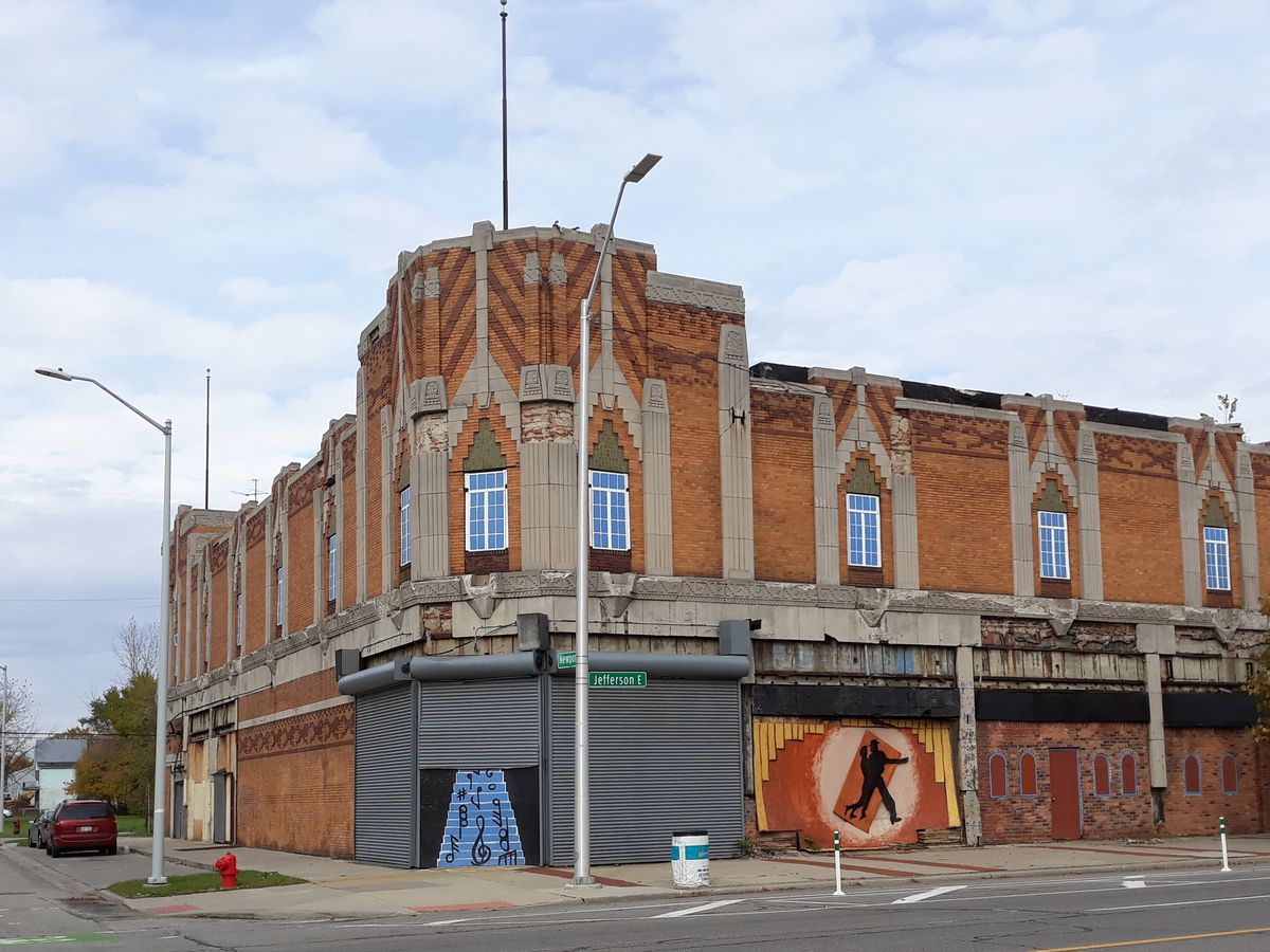 The exterior of the Vanity Ballroom in Detroit. The facade is red brick and has murals.