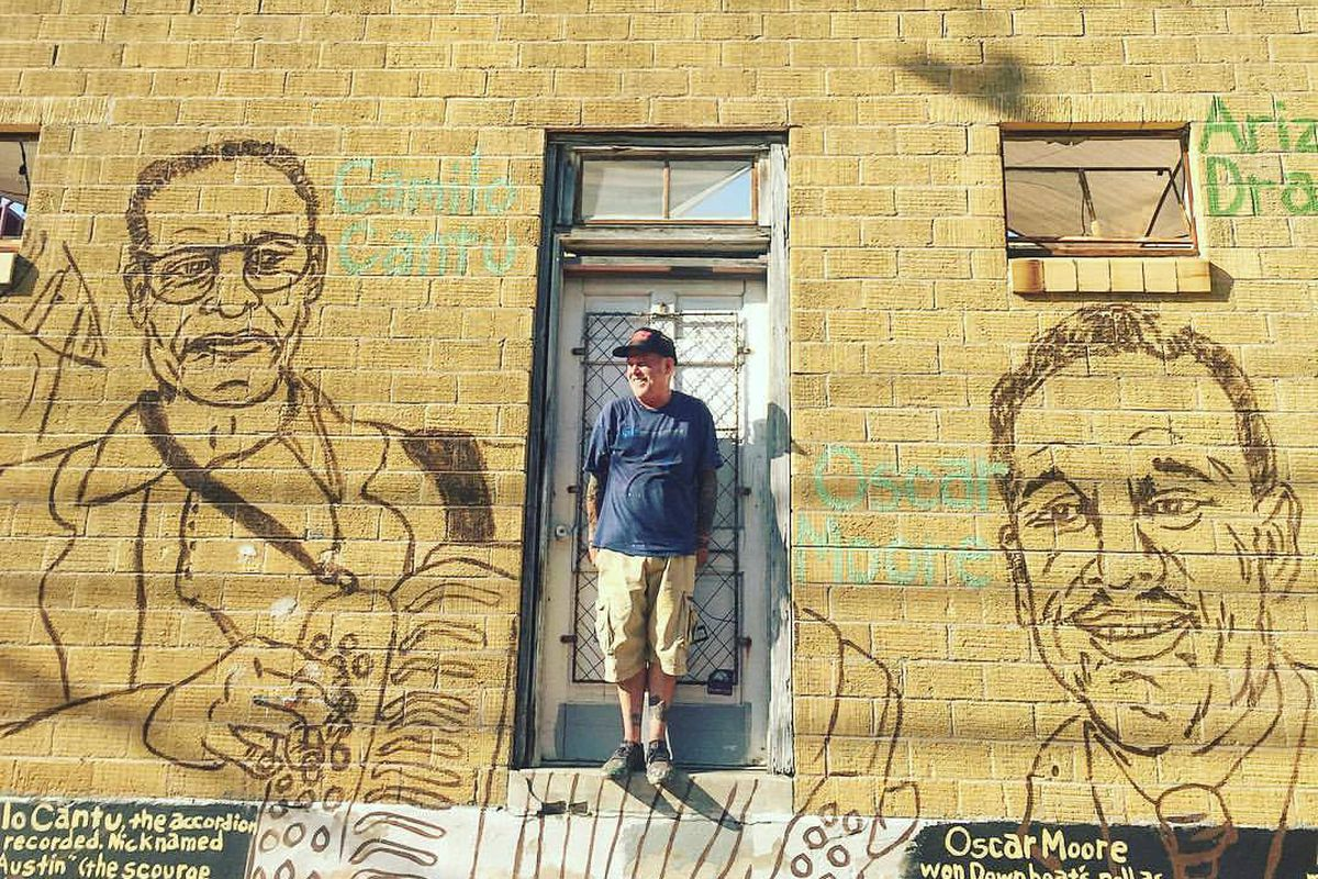 A man in ball cap, T-shirt and jeans in front of a yellow brick wall with a mural  of two men