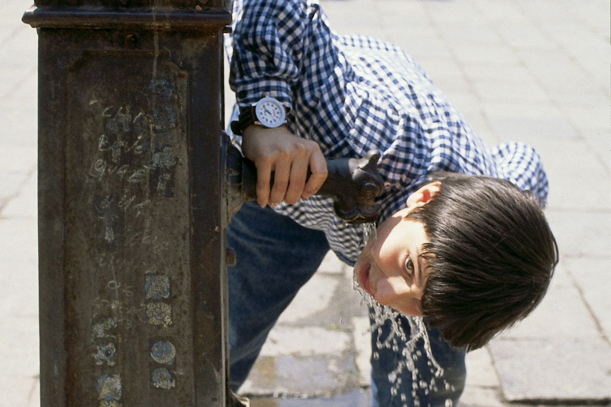 Boy drinking from a public water fountain