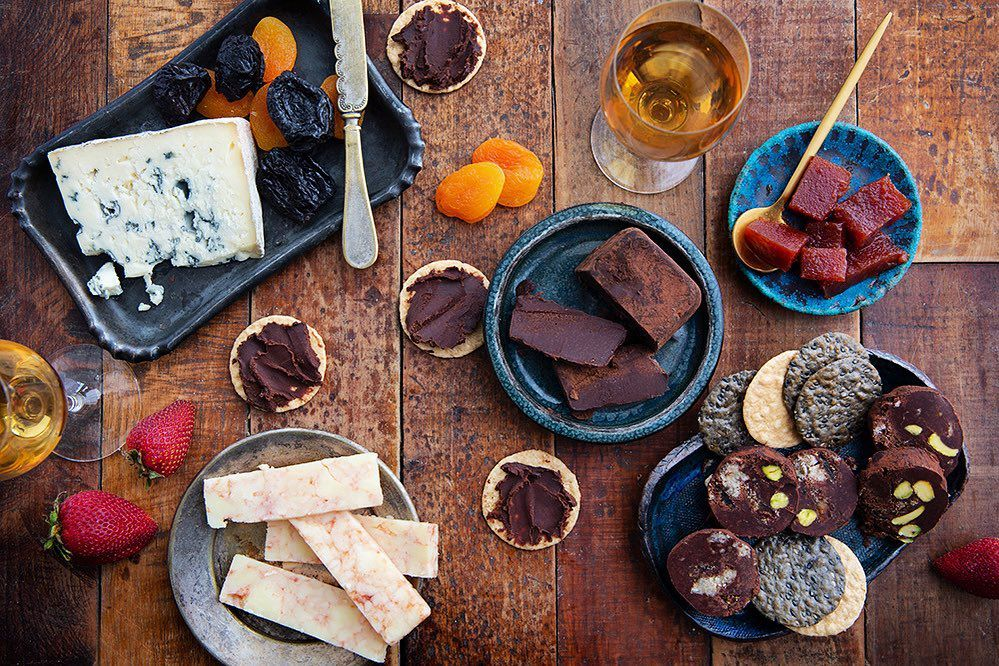A spread of Tavernier Chocolates, cookies, crackers, fruits, and cheeses on a wooden table.