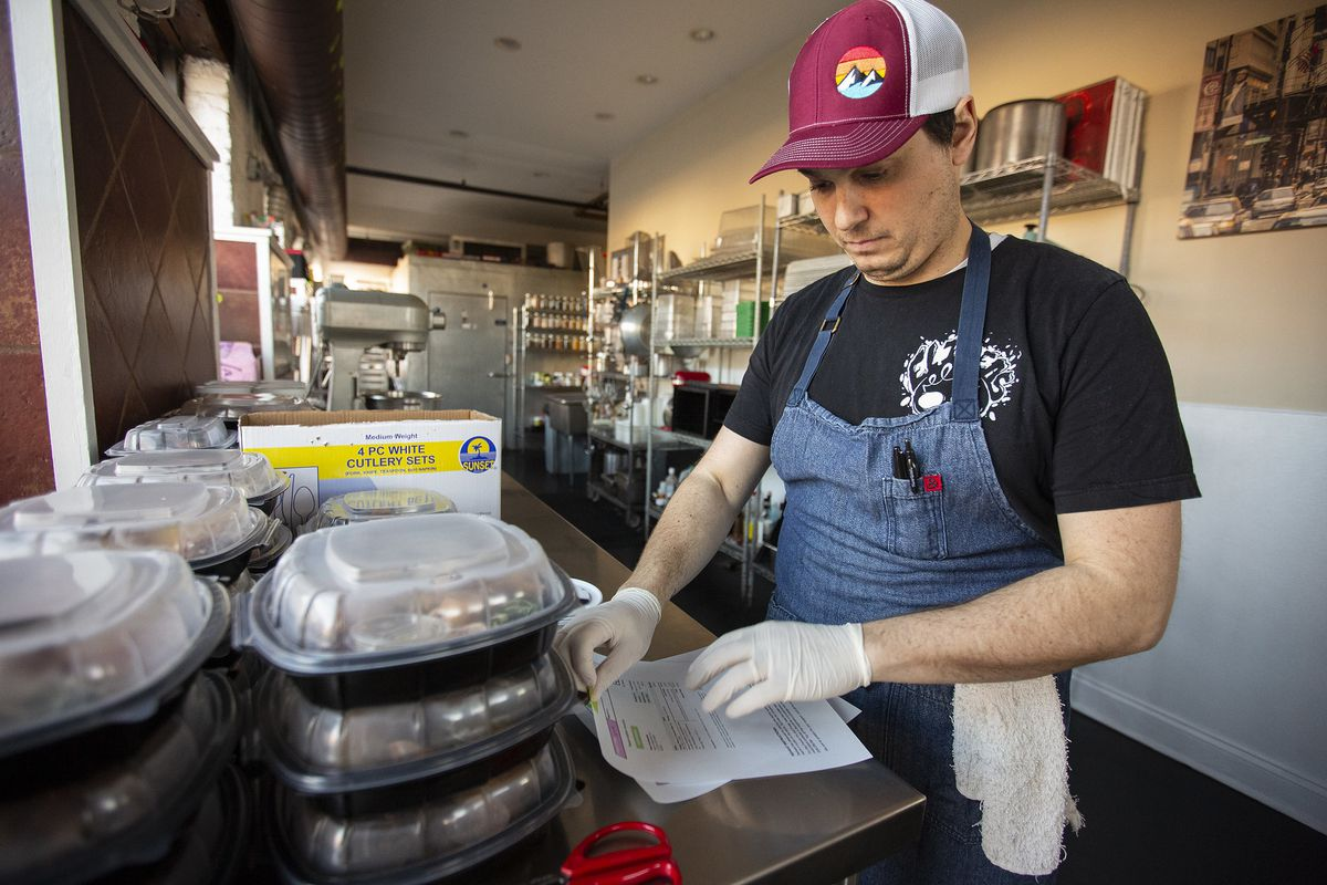 A person in a blue apron and baseball cap working in the kitchen.