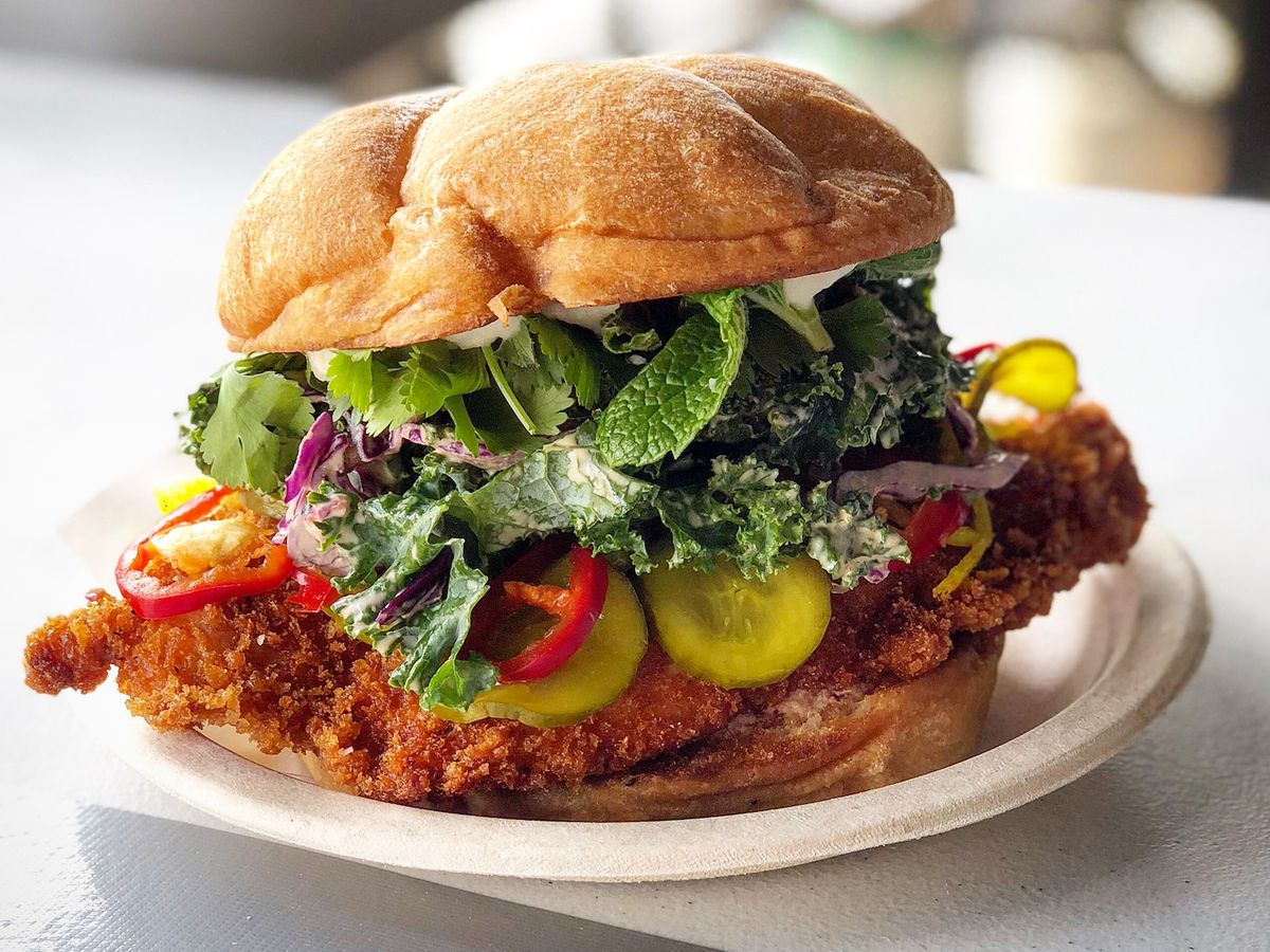 A big fried chicken sandwich with lots of greens from Banh Oui Melrose.