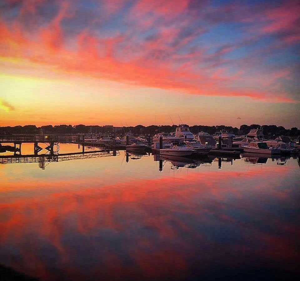 A colorful sunset over water in Quincy, Massachusetts, with docked boats visible in the water.