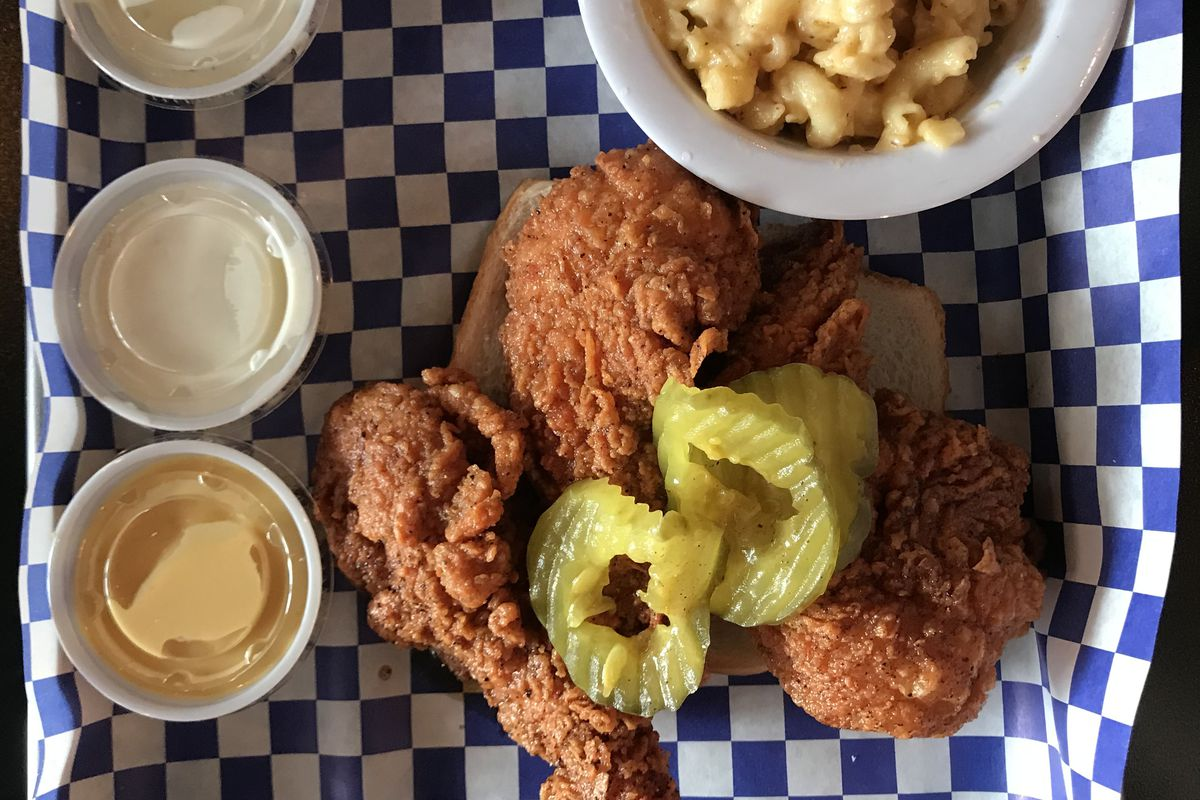 Nashville hot chicken on a blue checkered background with a side of macaroni and cheese