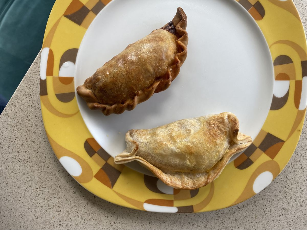 A mahogany-hued beef empanada and a lighter caprese one sit on a white and yellow decorative plate