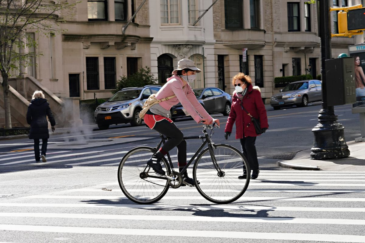 A woman in pink rides her bike across a sunny street; behind her, two older Americans bundled up in coats cross a crosswalk. All three are wearing masks.