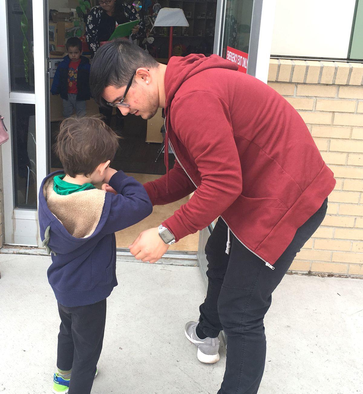 Julian Salazar, 18, helps a preschooler with his jacket during his internship.
