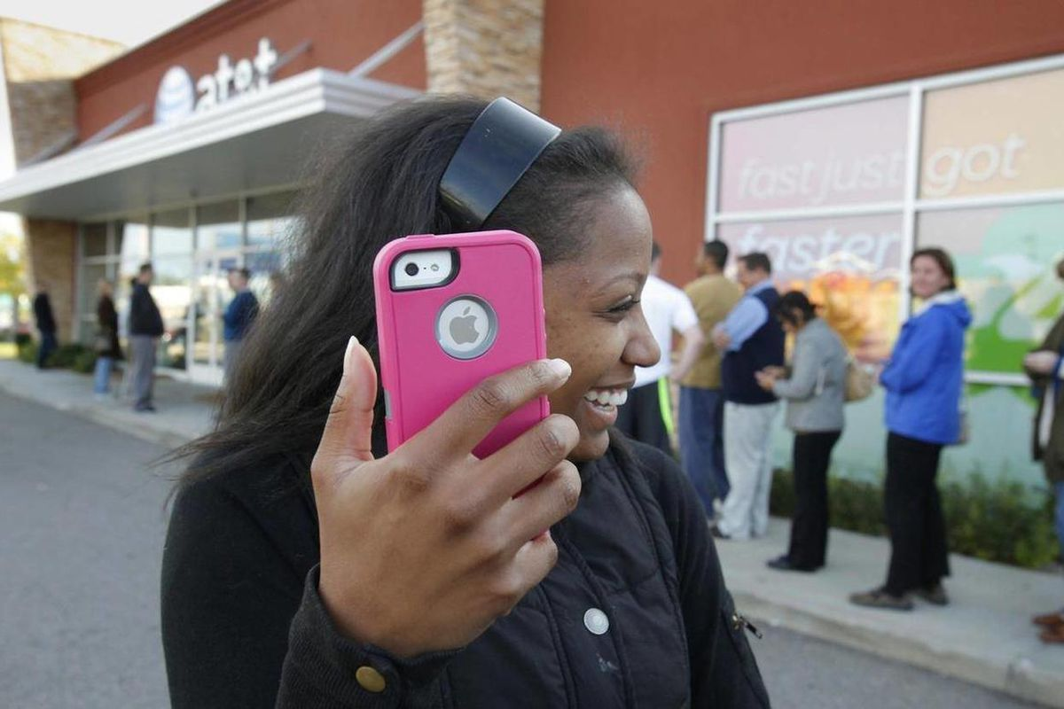Western Michigan University student Alenna Brown ,19, leaves with her new iPhone 5 in Kalamazoo, Mich. on Friday, Sept. 21, 2012.