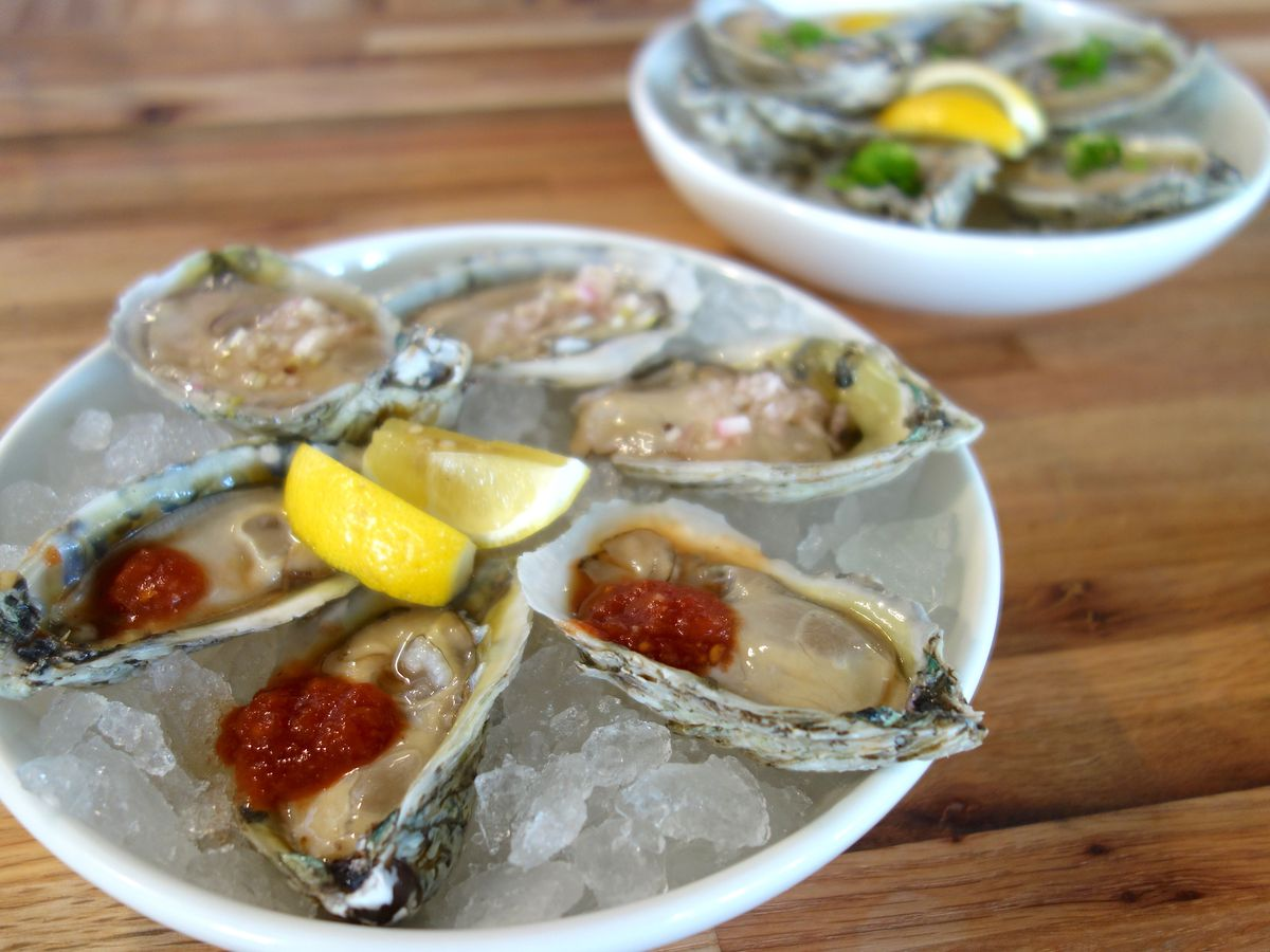 Raw oysters on the half shell over ice with lemon and cocktail sauce
