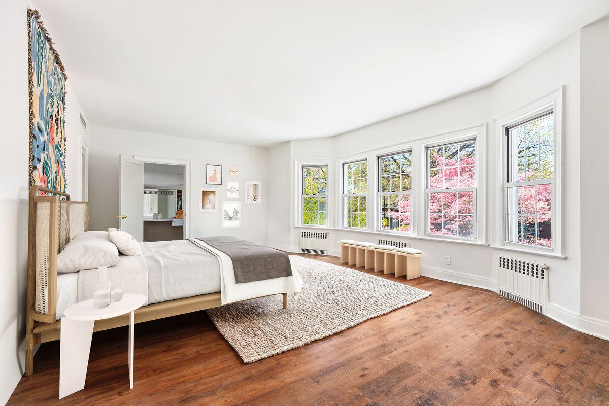 A large bedroom, hardwood floors, base moldings and five windows.