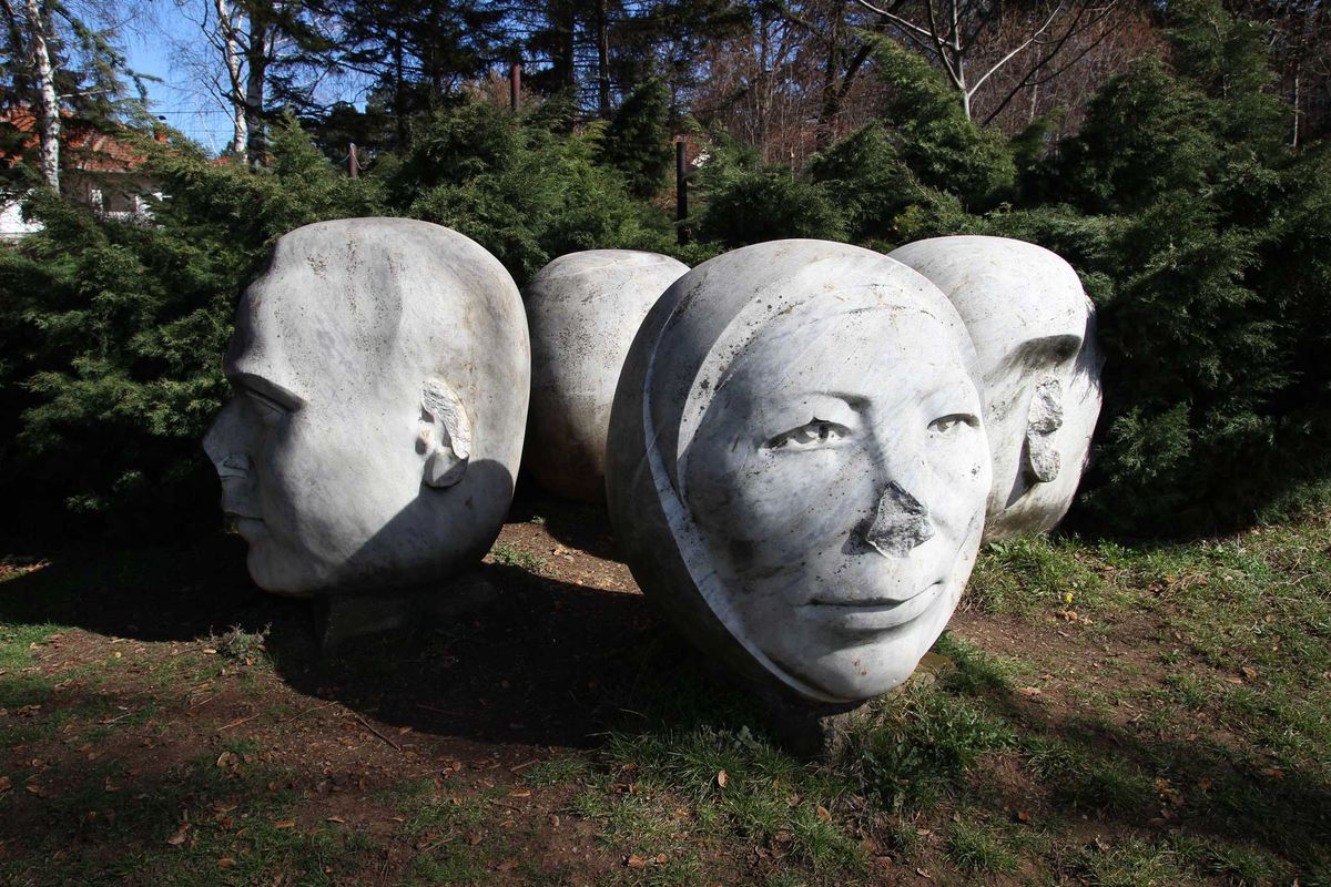 Cluster of stone head monuments on grass.