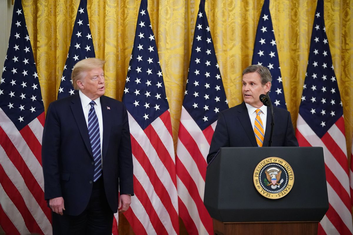 Then-President Donald Trump watches Tennessee Governor Bill Lee as he addresses the media at the White House. Lee makes remarks at a podium adorned with the Presidential Seal as six United States flags sit against a gold curtain in the background.