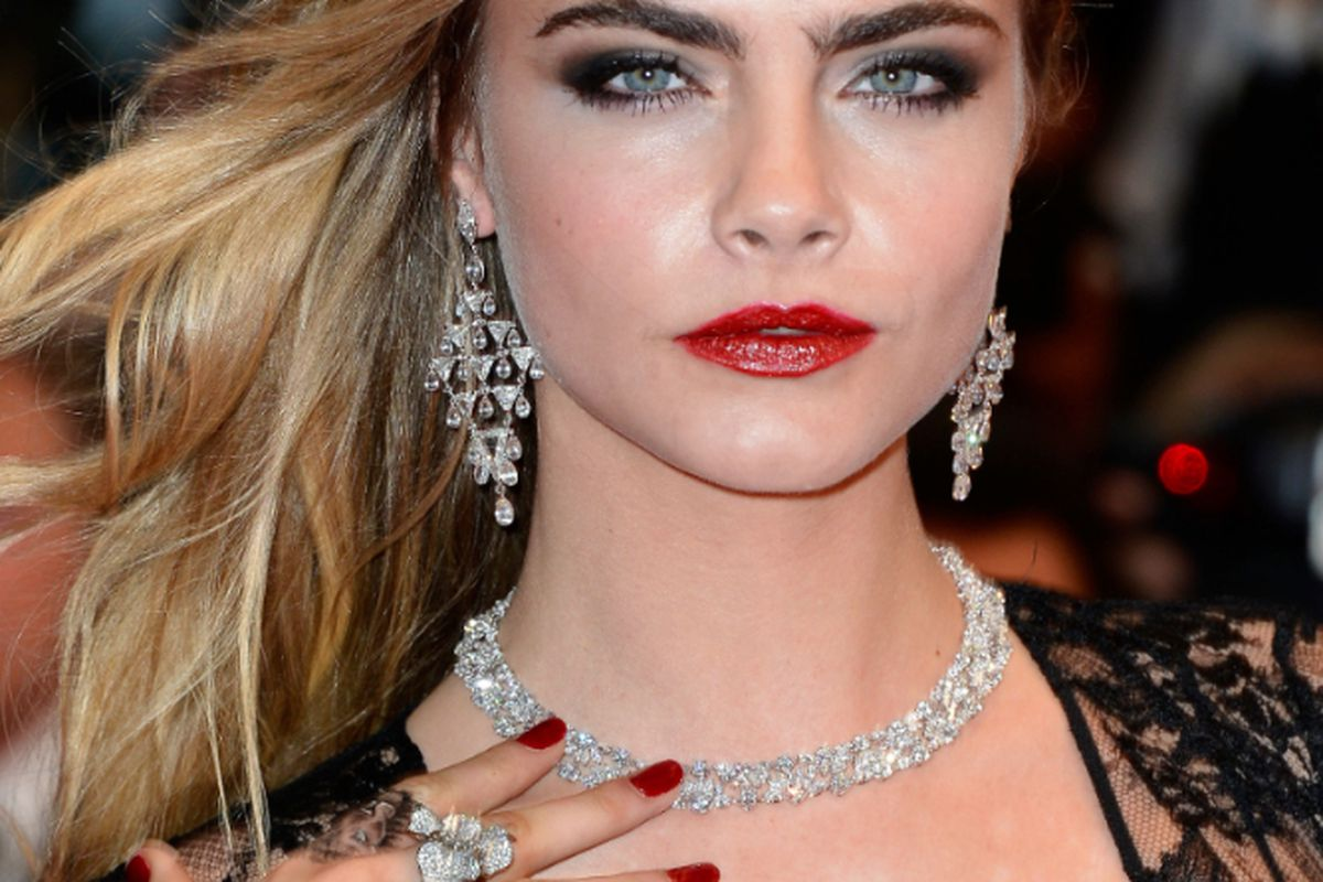 Cara Delevingne showing off borrowed Chopard diamonds (and a new lion finger tatt) in Cannes, image via Getty