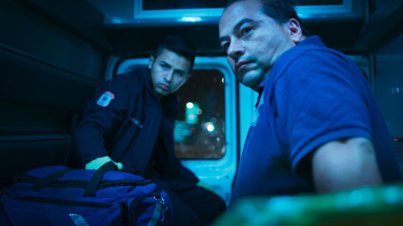 Two men outside an ambulance in Midnight Family.