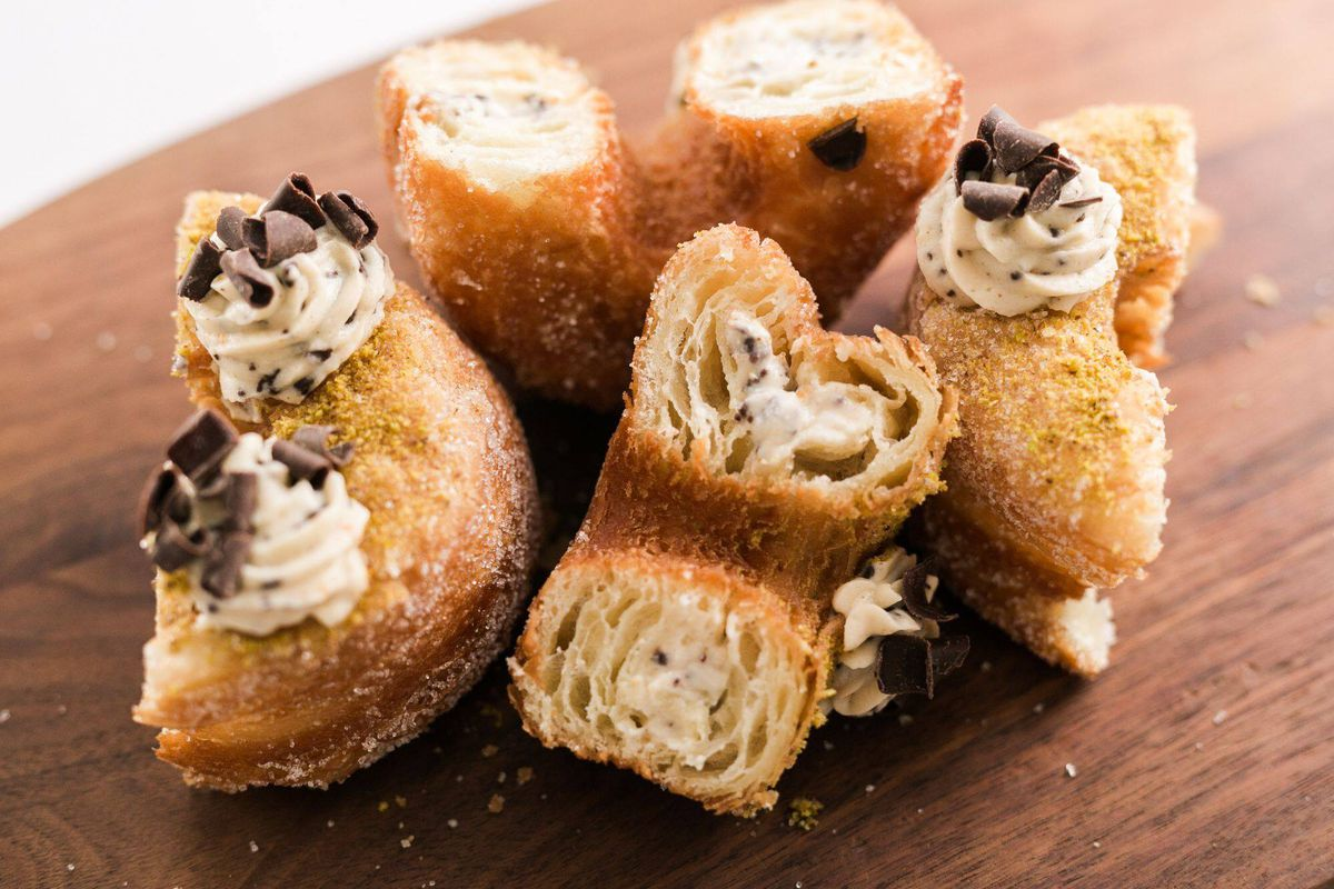 Two 100 layer doughnuts cut in half filled with Cannoli cream
