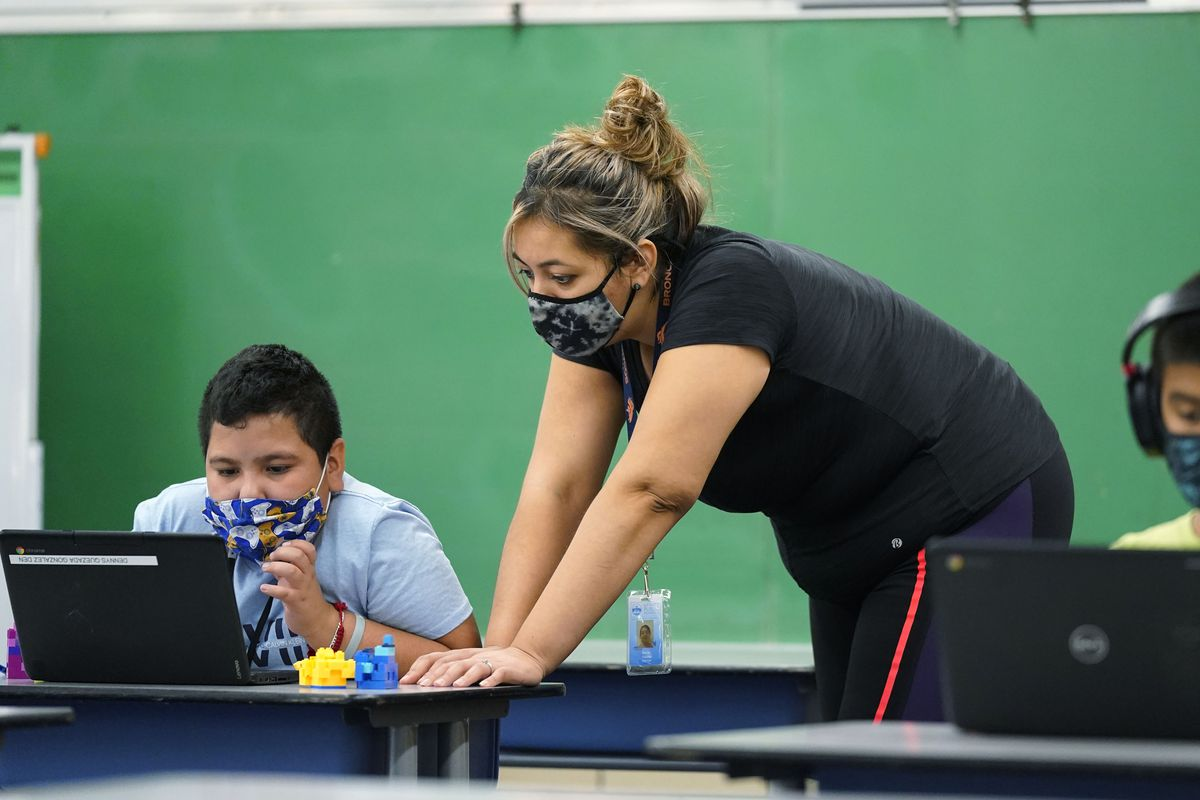 Masked teacher helps masked students who are working on laptops.