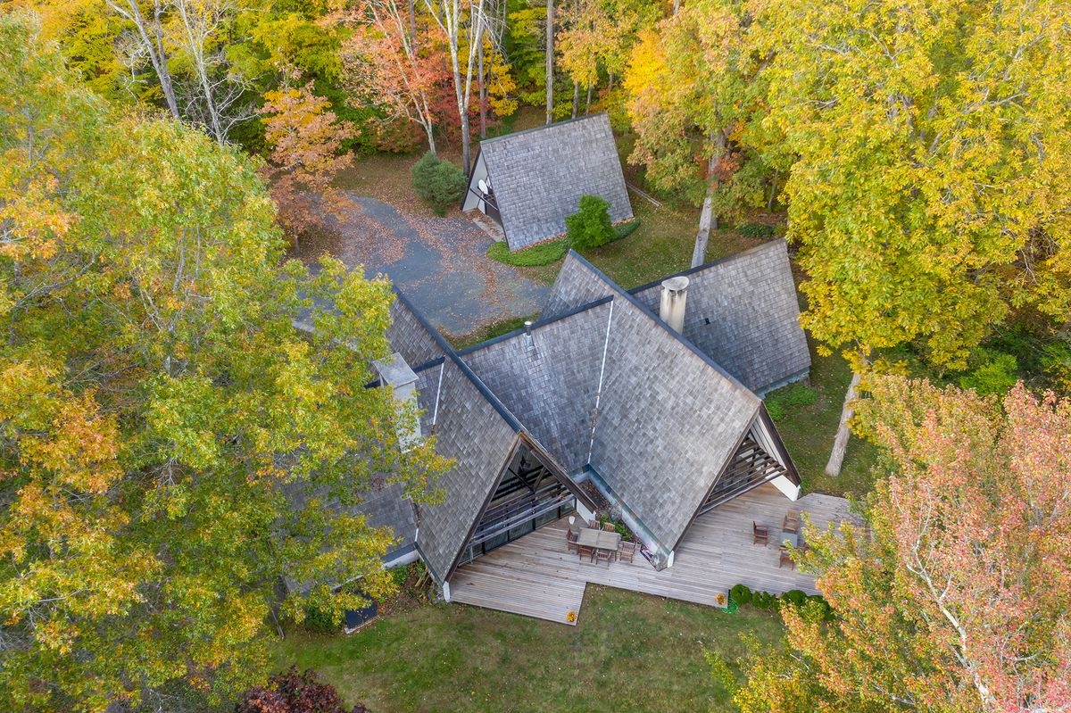 An aerial view of an A-frame house with trees surrounding it.