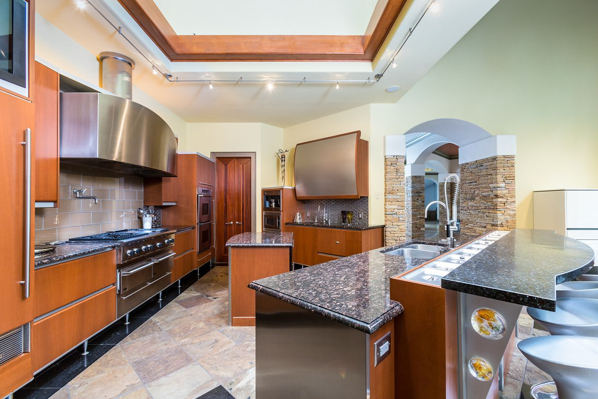A huge kitchen with granite counters everywhere and tile flooring.