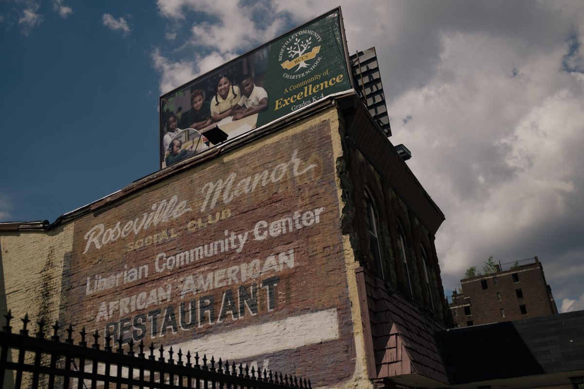 """A mural on the side of a brick wall reads """"Roseville Manor Social Club, Liberian Community Center, African American Restauraunt"""". Atop the wall, there is a billboard for Roseville Community Charter School."""