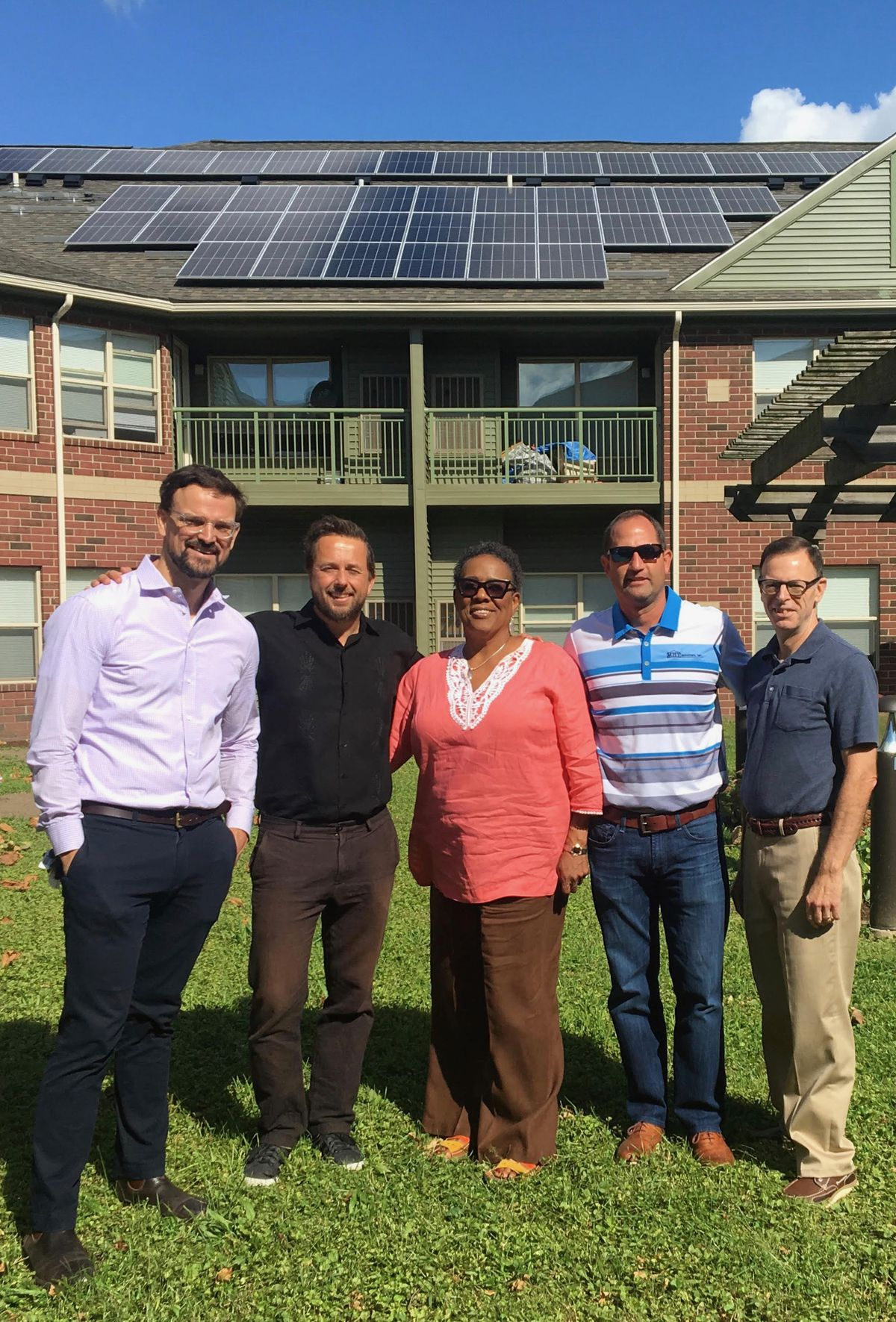 Five people stand smiling in a grassy courtyard on a sunny day. The four men are white and the one woman in the middle is black.