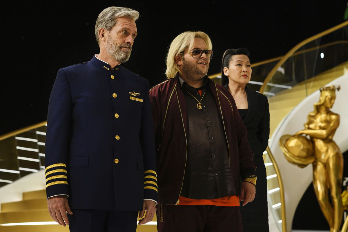 Hugh Laurie as spaceship captain Ryan Clark and Josh Gad as smarmy-looking billionaire ship owner Herman Judd stand together on their luxury cruise spaceship.