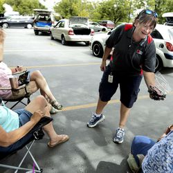 Sherry Munsell, a truck driver for the Utah Food Bank, offers cherries to a group of women as they wait in line at the Utah Food Bank mobile pantry at The Church of Jesus Christ of Latter-day Saints Cannon Stake Center in Salt Lake City on Wednesday, June 9, 2021.