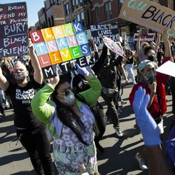 """Protestors hold up signs during the """"Drag March for Change"""" on Halsted Street in Lakeview, Chicago, Sunday, June 14, 2020."""