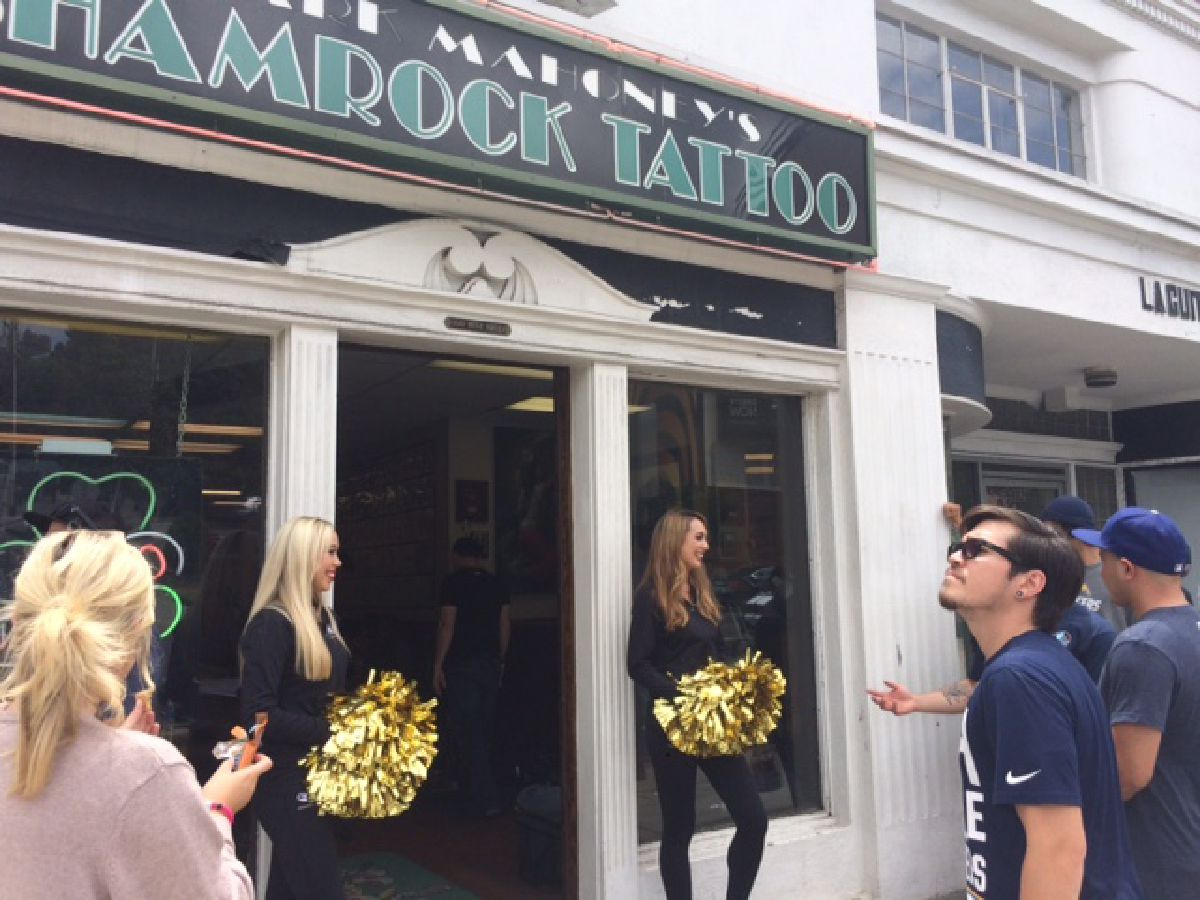 Cheerleaders stand outside the Shamrock Social Club as fans line up for free Chargers tattoos