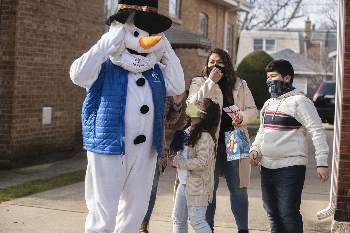 A masked Frosty greets the Jimenez family on Sunday as part of Operation Santa.