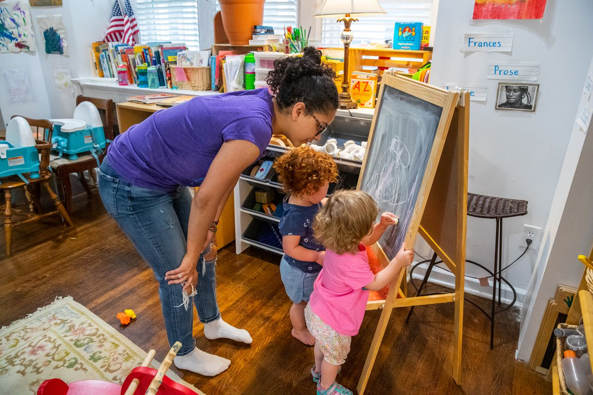 Justice Vaughn (left), daughter of Cynthia Randolph-Vaughn of Cindy's Center For Young Learners, helps students, Prose VanVeelen (middle), 2, and Frances Stratman, 1, color with chalk on Wednesday, May 29, 2019.