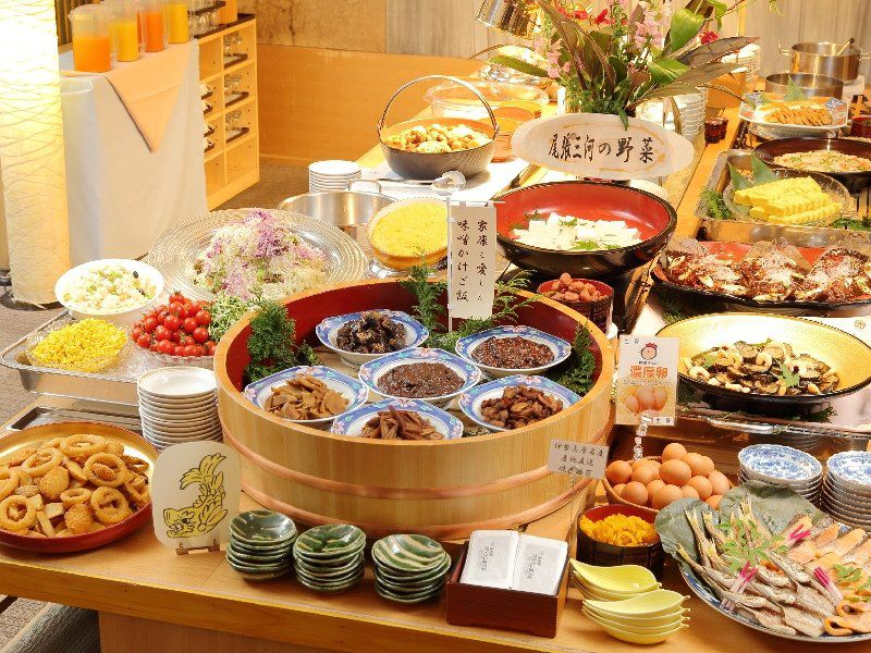 A buffet table loaded with steamer boxes, colorful ceramic dishes, and serving plates topped with various Japanese foods including fish, fried items, and vegetables