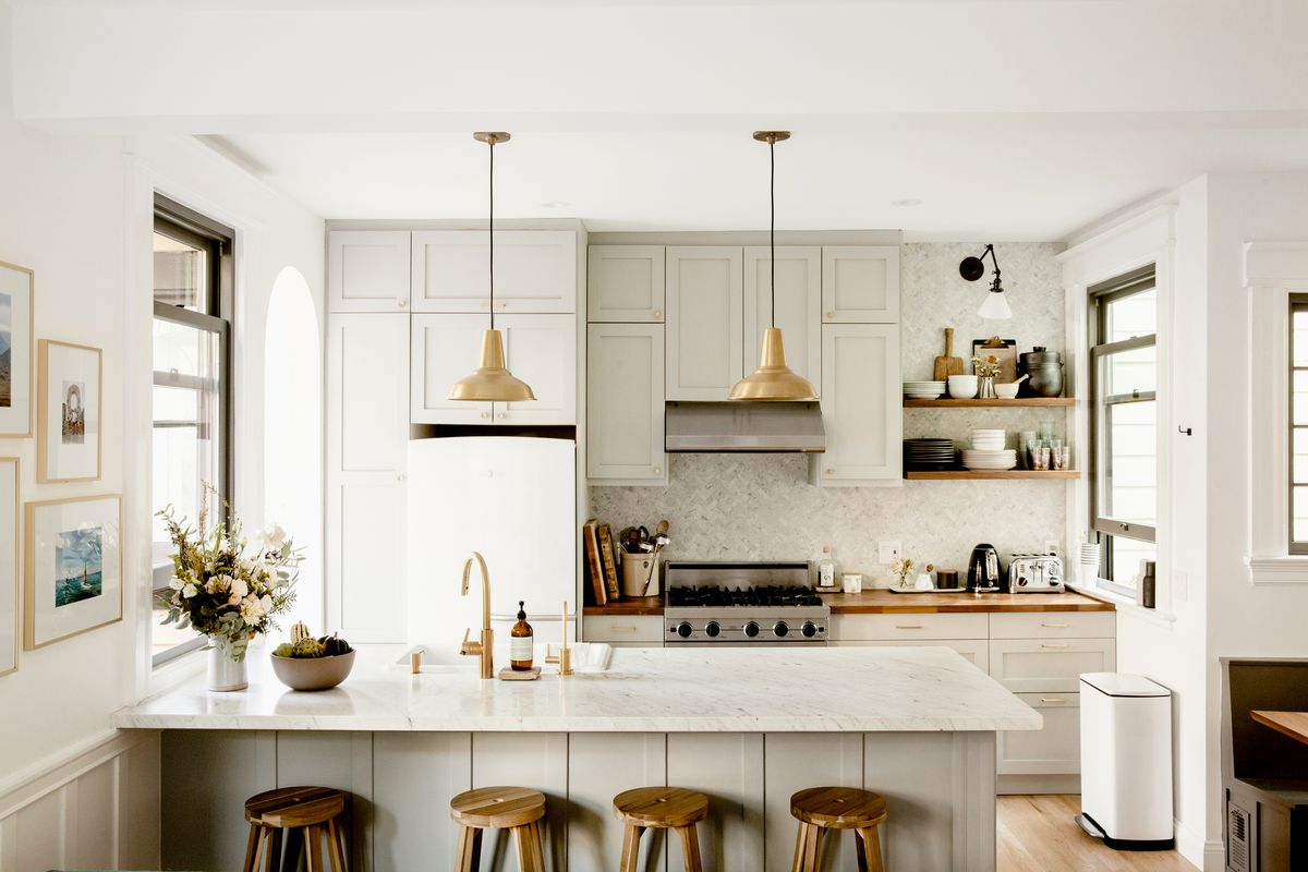 A bright kitchen with white marble island, white cabinets, and a stainless steel oven. Two bronze pendant lamps hang over the island.