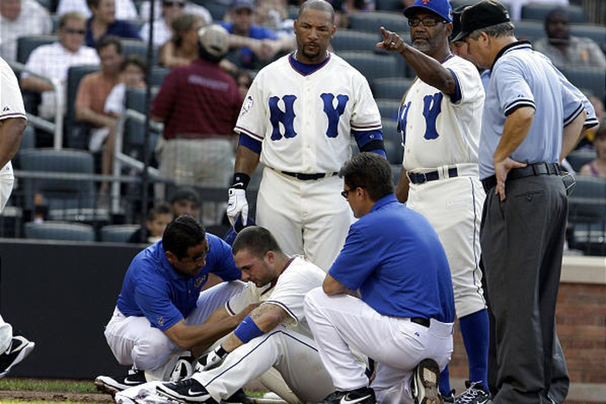New York Mets' David Wright is checked out by trainers at home plate after being hit by a pitch thrown by San Francisco Giants' Matt Cain as Gary Sheffield, above center, and manager Jerry Manuel, second from right, look on.