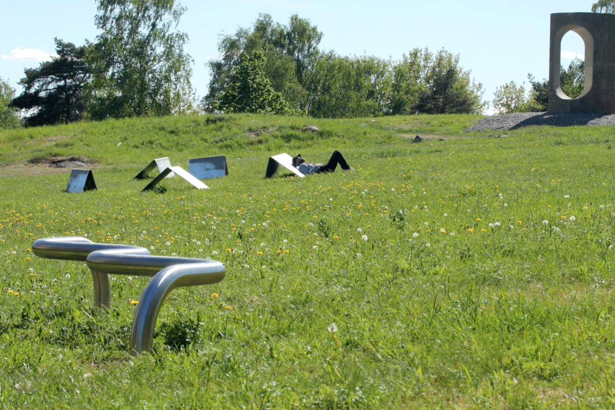 A curving metal bench, folded metal partitions, and a concrete structure placed in a grassy field.