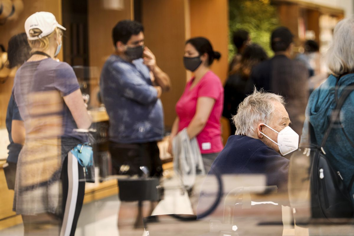 In a busy store, customers wait in line, all wearing masks.