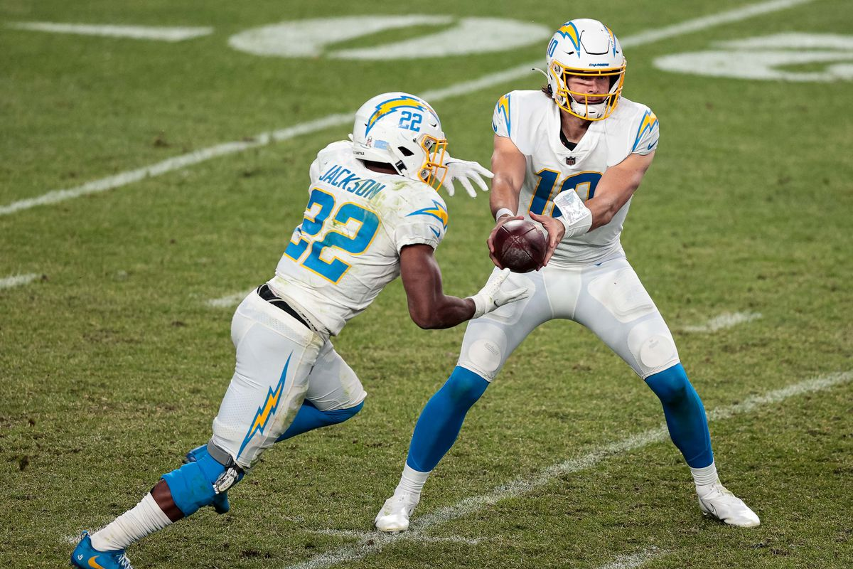 Los Angeles Chargers quarterback Justin Herbert (10) hands the ball off to running back Justin Jackson (22) in the fourth quarter against the Denver Broncos at Empower Field at Mile High. Mandatory Credit: Isaiah J. Downing