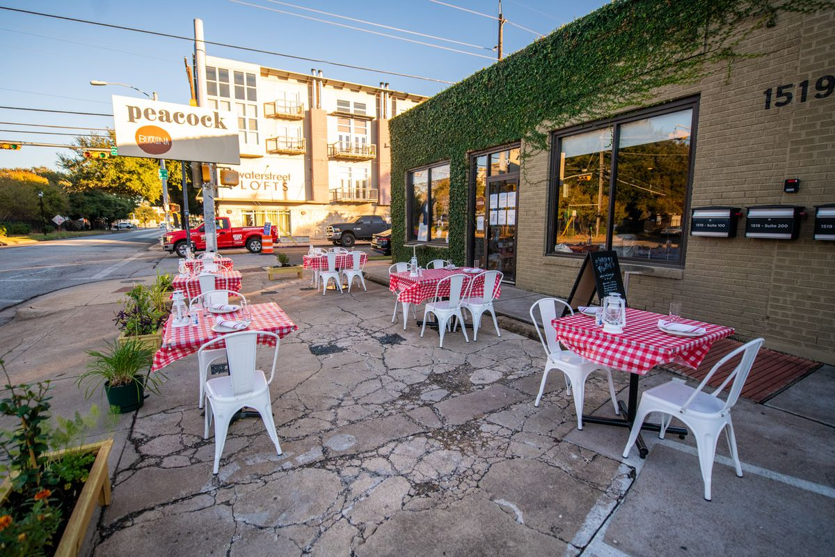 A parking lot with two-person tables with red-and-white checkered tablecloths and white chairs outside of a building covered in green ivy plants