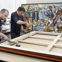 """Thierry Boutet, left, and Hugh Glover work on framing one of six enormous Hale Woodruff murals at the Atlanta Conservation Center on April 25, 2012. A crew has spent many months of preservation work on the murals that will be the focal of the High Museum of Art exhibit (opening June 6), """"Rising Up: Hale Woodruff's Murals at Talladega College."""" (Phil Skinner/Atlanta Journal-Constitution/MCT)"""