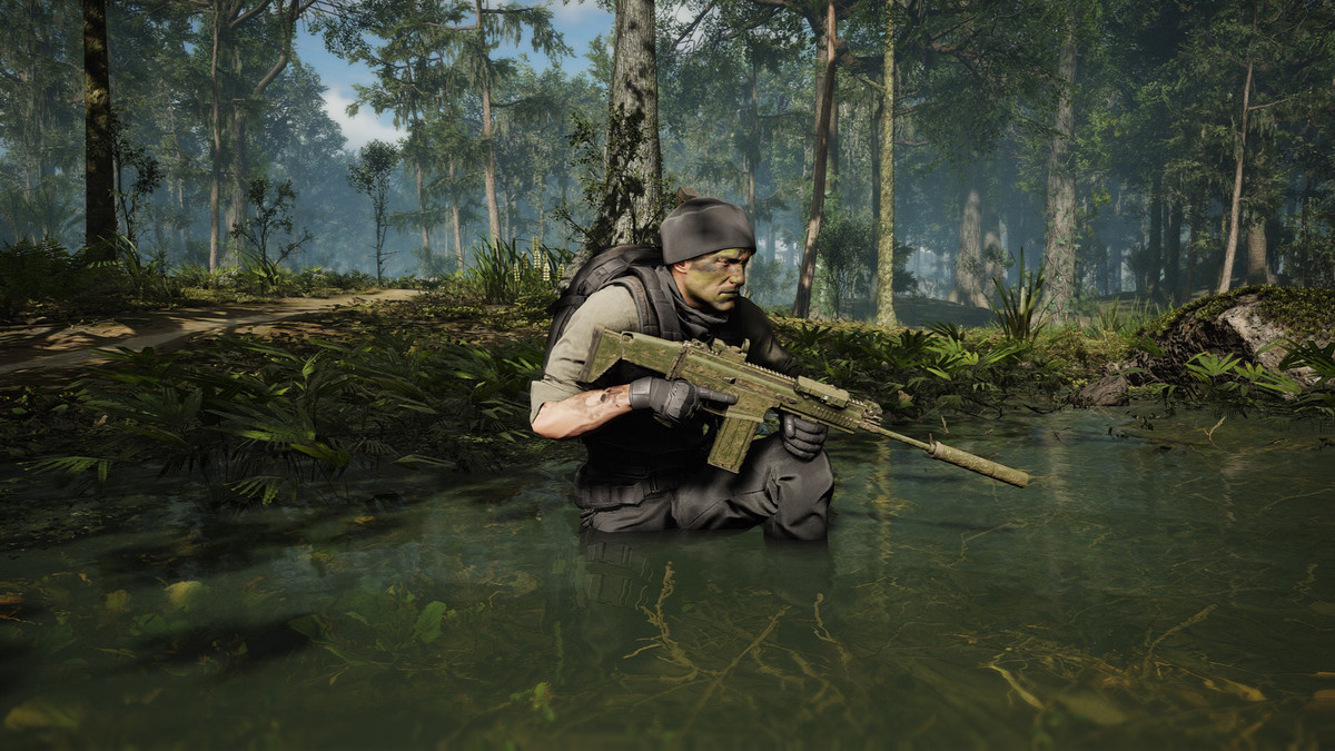 A soldier in a gray beanie, holding a green assault rifle, crouches in a swamp