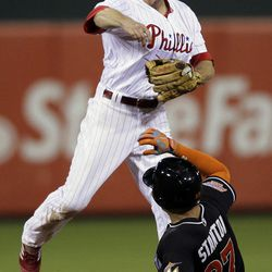 Philadelphia Phillies' Chase Utley, top, throws to first base on a double play after forcing out Miami Marlins' Giancarlo Stanton at second in the ninth inning of a baseball game, Monday, Sept. 10, 2012, in Philadelphia. Miami's Carlos Lee was out at first. Philadelphia won 3-1.