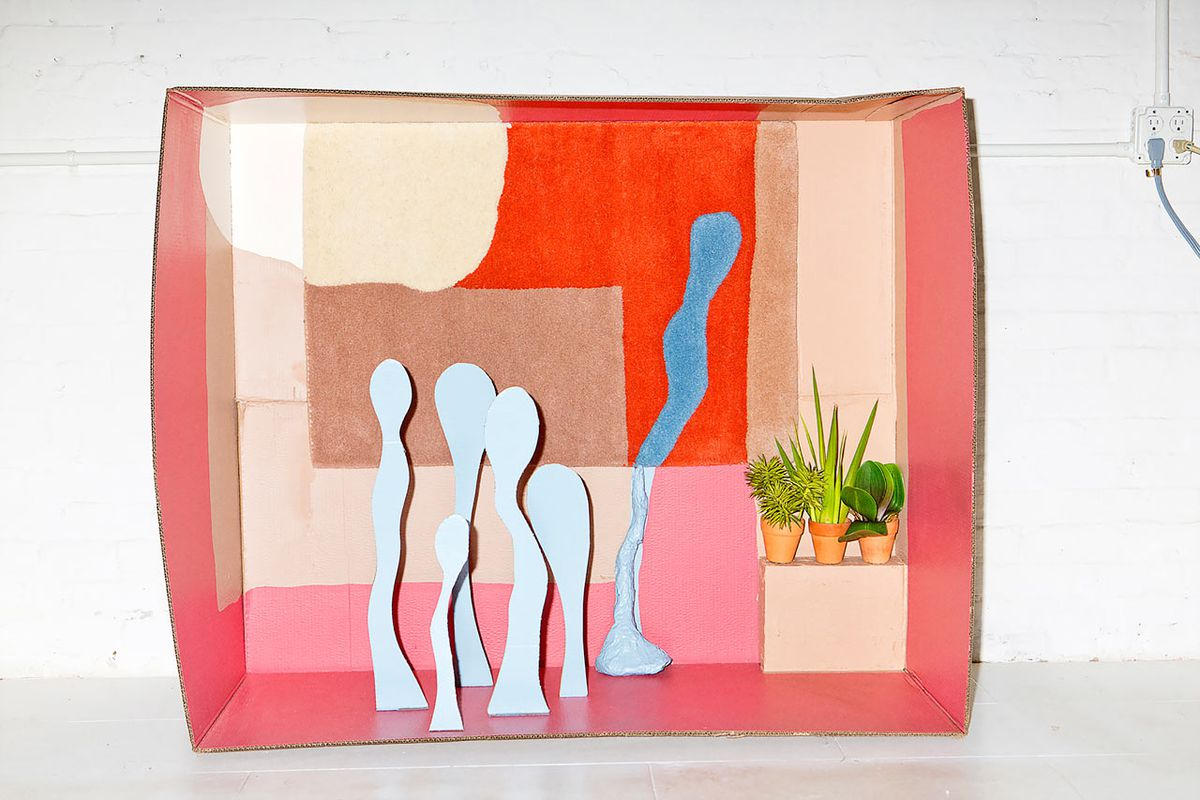 A rug with abstract shapes is placed within a cardboard diorama with its shapes appearing to bleed into physical forms outside of it.