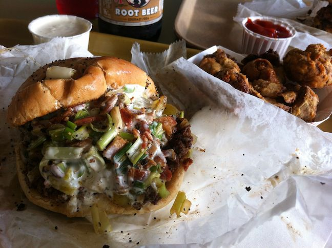 An extremely messy burger on wax paper.