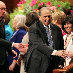 As he leaves the Conference Center podium, President Thomas S. Monson shakes hands with Sisters Linda K. Burton and Emri Elizabeth Smith, who offered the opening prayer in the General Women's Meeting on Saturday, March 29, 2014. Behind him are his counselors, President Henry B. Eyring and President Dieter F. UIchtdorf.