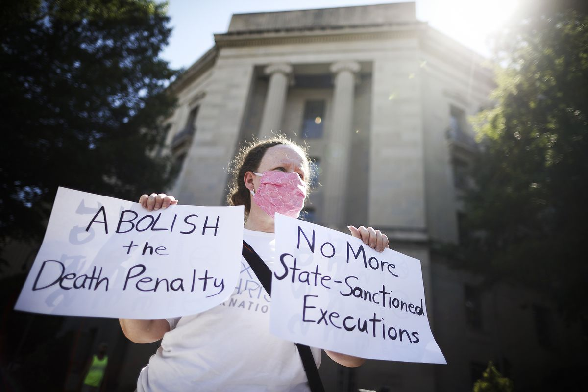 """A person standing in front of the Justice Department building holds signs that read """"Abolish the death penalty"""" and """"No more state-sanctioned executions."""""""