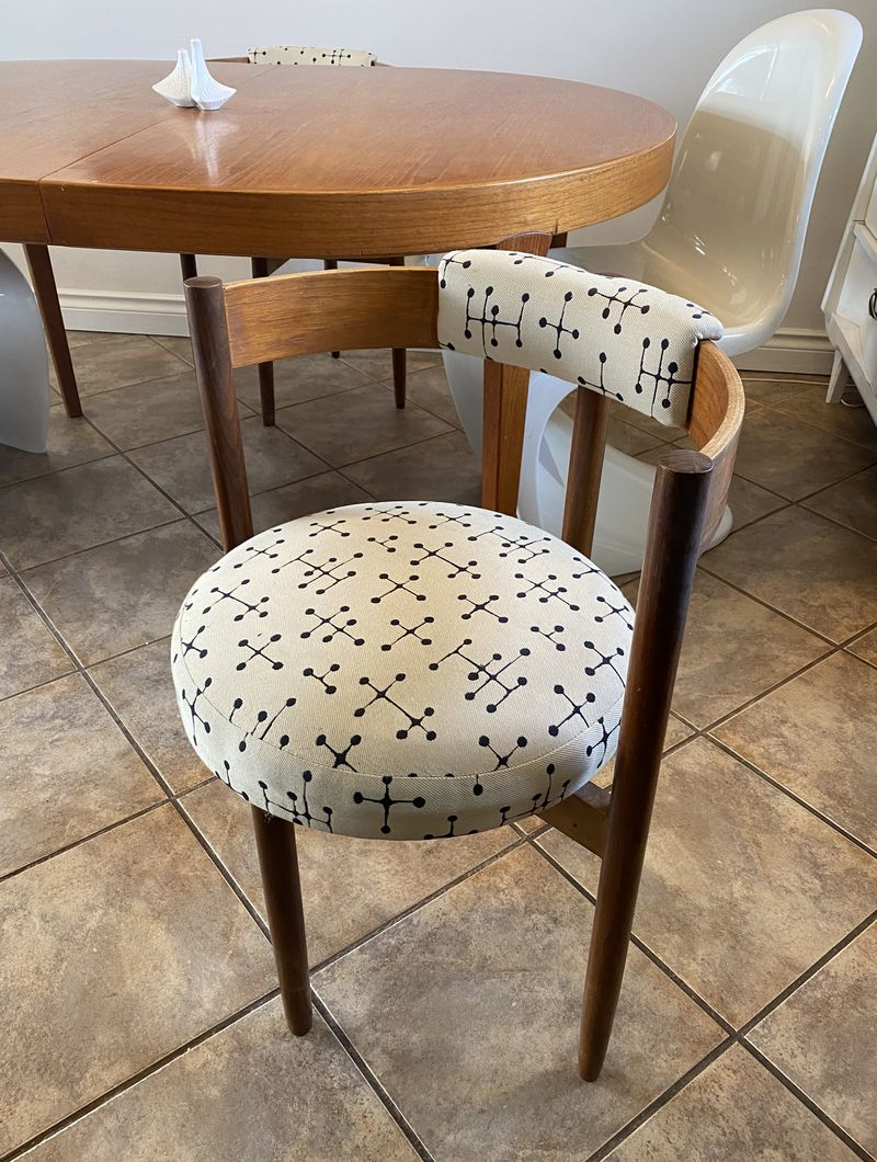 A chair with semi-circular wooden back and cream-colored cushioned seat with black dot pattern.
