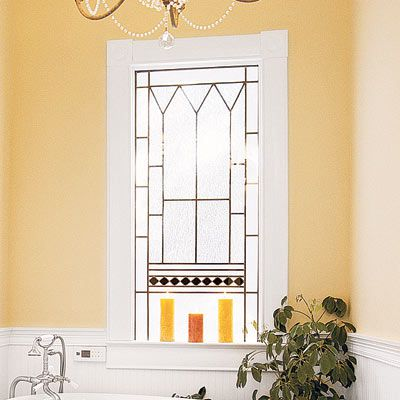 Bathroom window with gold detail and candles on the small window sill.